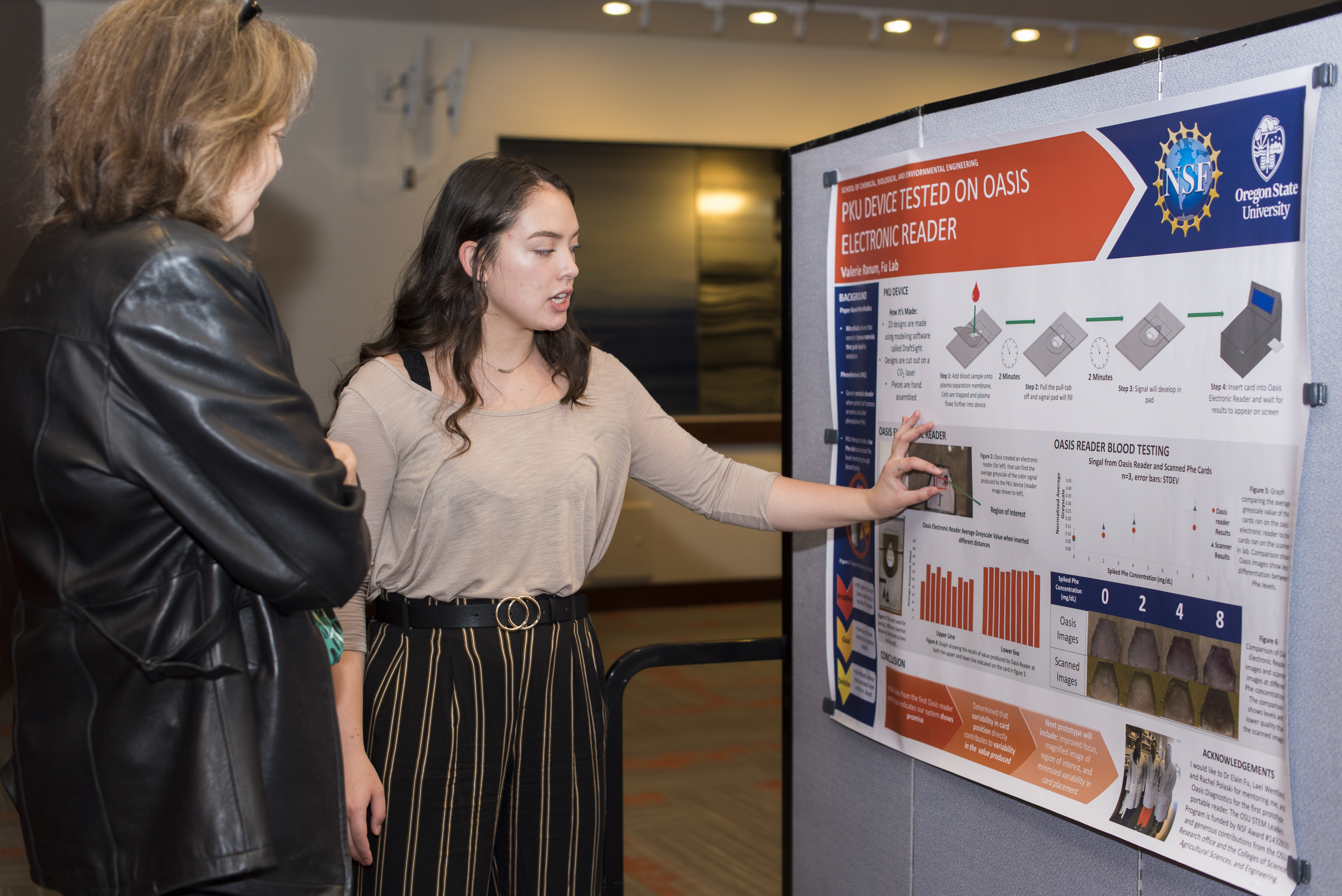 "Female student presenting her research poster titled ""PKU Device Tested on Oasis Electronic Reader"" to a woman"